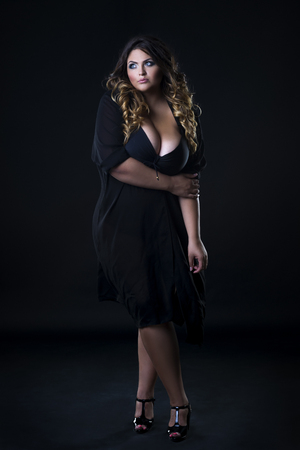 Young beautiful caucasian plus size model in underwear, xxl woman on black background, full length portrait