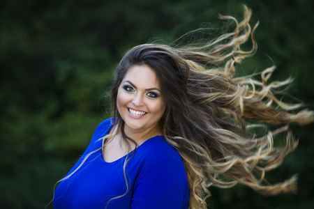 Young beautiful caucasian plus size model in blue dress outdoors, xxl woman on nature with developing in the wind hair, professional makeup and hairstyle Фото со стока - 62247819