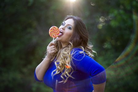 Young beautiful caucasian plus size model in blue dress outdoors, xxl woman on nature licking a lollipop, professional makeup and hairstyle