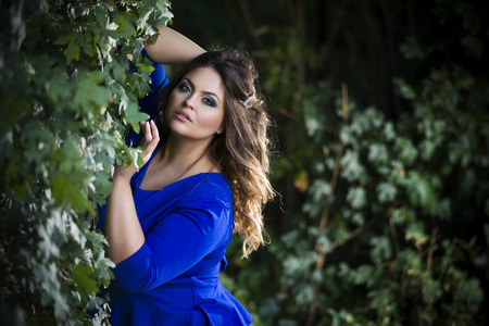 Young beautiful caucasian plus size model in blue dress outdoors, xxl woman on nature, professional makeup and hairstyle