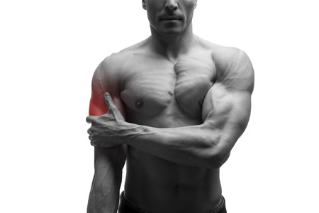 Man with pain in shoulder, ache in muscular male body, isolated on white background with red dot, black and white photo Stock Photo