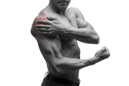 shoulder inflammation: Man with pain in shoulder, ache in muscular male body, isolated on white background with red dot, black and white photo Stock Photo