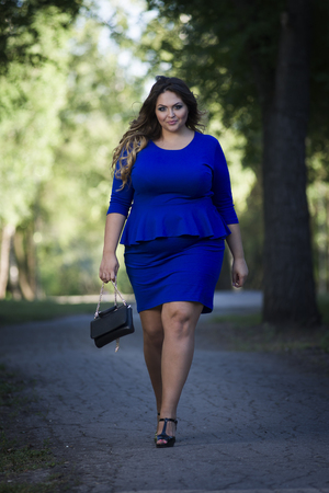 Young beautiful caucasian plus size fashion model in blue dress outdoors, xxl woman on nature, full length portrait