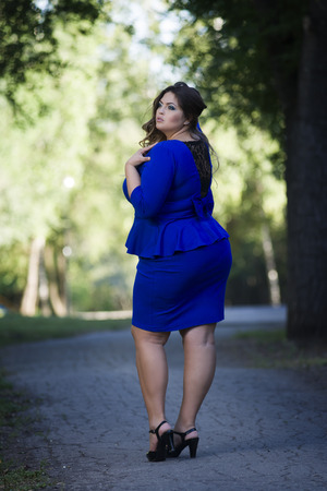Young beautiful caucasian plus size fashion model in blue dress outdoors, xxl woman on nature, full length portrait, back view