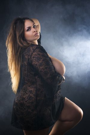 Young naked beautiful caucasian plus size model, xxl woman in black peignoir on smoky studio background, beauty female nude body with big breast Фото со стока