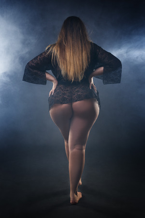 Young naked beautiful caucasian plus size model, xxl woman in black peignoir on smoky studio background, beauty female nude body with big buttocks and hips