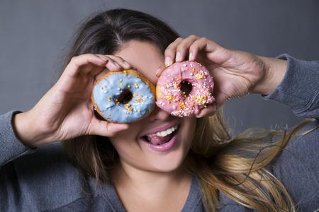 회색 스튜디오 배경에 도넛과 함께 포즈 행복 아름 다운 젊은 백인 플러스 사이즈 모델, 패스트 푸드와 건강에 해로운 영양 개념 스톡 콘텐츠