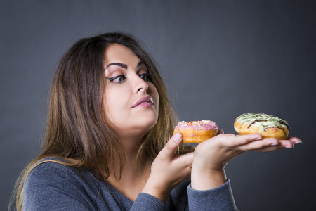 Beautiful young caucasian plus size model posing with donuts on a gray studio background, fast food and unhealthy nutrition concept