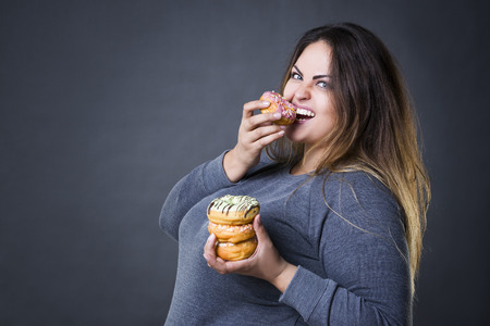Happy beautiful young caucasian plus size model posing with donuts on a gray studio background, fast food and unhealthy nutrition concept Фото со стока - 63831538