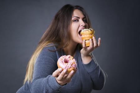 Happy schöne junge kaukasisch-Modell plus Größe mit Donuts auf einem grauen Hintergrund Studio, Fast Food und ungesunde Ernährungskonzept aufwirft