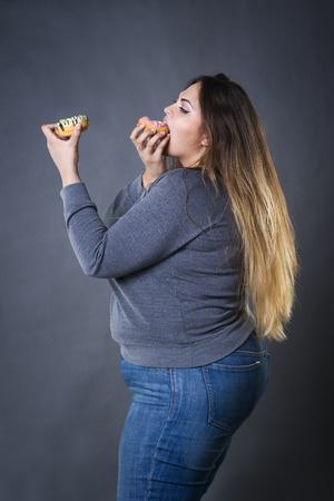 Beautiful young caucasian plus size model posing with donuts on a gray studio background, fast food and unhealthy nutrition concept Фото со стока - 63831544