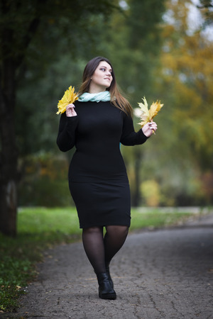 Young beautiful caucasian plus size model in black dress outdoors, xxl woman on nature, autumn atmosphere, plump women Stock Photo
