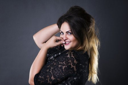Young beautiful plus size model in black lace dres, xxl woman portrait on gray studio background, makeup and hairstyle