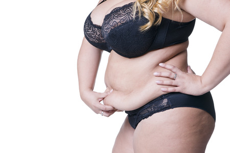Plus size model in black lingerie, overweight female body, fat woman with flabby stomach posing isolated on white background