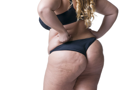 Plus size model in black lingerie, overweight female body, fat woman with cellulitis on buttocks posing isolated on white background, back view Stock Photo