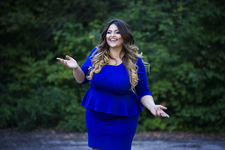 Young happy smiling beautiful plus size model in blue dress outdoors, xxl woman on nature, professional makeup and hairstyle Stock Photo