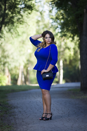 Young beautiful stylish plus size fashion model in blue dress outdoors, xxl woman on nature, full length portrait, professional makeup and hairstyle Фото со стока - 68162626