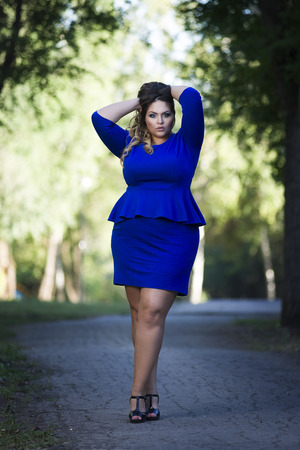 Young beautiful stylish plus size fashion model in blue dress outdoors, xxl woman on nature, full length portrait, professional makeup and hairstyle Фото со стока - 68162627