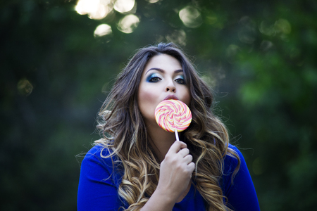 Young beautiful plus size model in blue dress outdoors, xxl woman on nature licking a lollipop, professional makeup and hairstyle Stock Photo