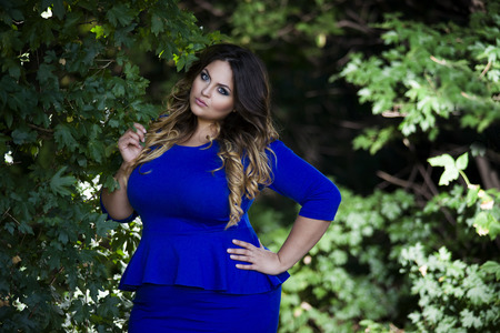 Young beautiful plus size model in blue dress outdoors, xxl woman on nature, professional makeup and hairstyle Stock Photo