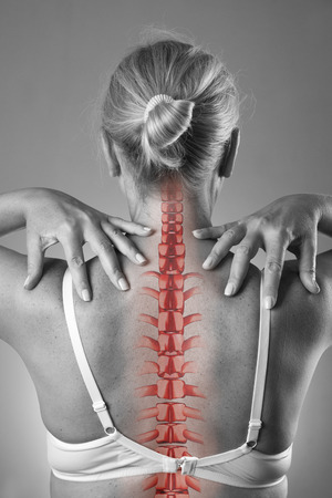 Spine pain, woman with backache and ache in the neck, black and white photo with red backbone on gray background Standard-Bild