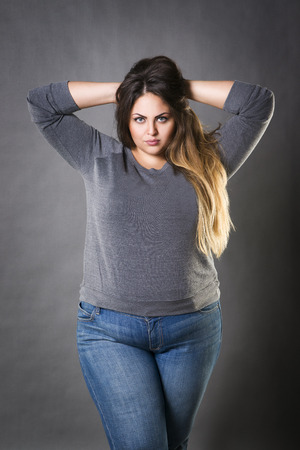Young beautiful plus size model in blue jeans, xxl woman on gray studio background 版權商用圖片
