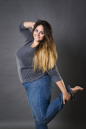 Young beautiful plus size model in blue jeans, xxl woman on gray studio background Stock Photo