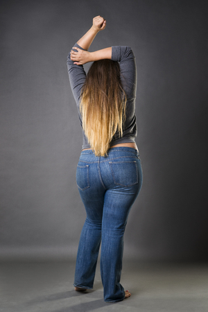 Plus size model in blue jeans, xxl woman on gray studio background, full length