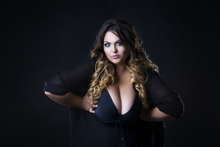 Young beautiful plus size model in underwear, xxl woman on black background, professional makeup and hairstyle