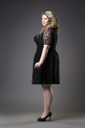 Young beautiful plus size model in black dres, xxl woman on gray studio background, full length portrait Banco de Imagens