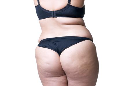 Plus groottemodel in zwarte lingerie, te zwaar vrouwelijk lichaam, vette vrouw met cellulitis bij het billen stellen geïsoleerd op witte achtergrond, achtermening