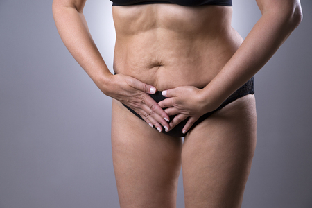 cystitis: Woman with menstrual pain, endometriosis or cystitis, stomach ache on gray background