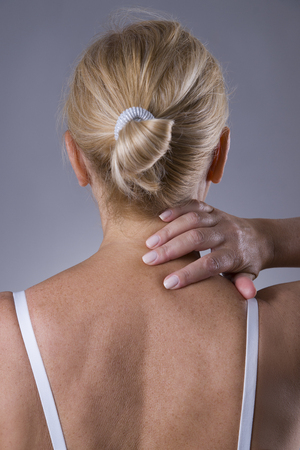 Neck pain, massage of female body, ache in womans body on gray background