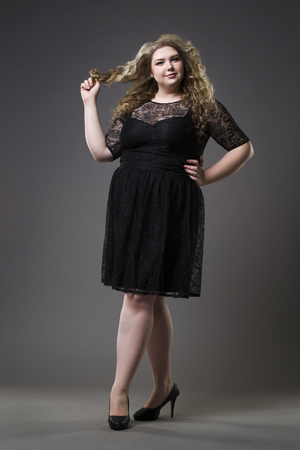 Young beautiful plus size model in black dres, xxl woman on gray studio background, full length portrait Stock Photo