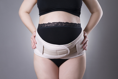 belly bandage: Pregnant woman in black underwear with orthopedic support belt, pregnancy bandage, studio shot on gray background