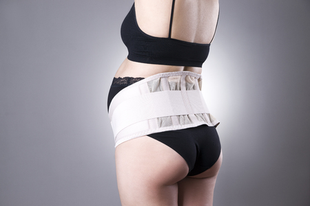 belly bandage: Pregnant woman in black underwear with orthopedic support belt, pregnancy bandage, studio shot on gray background, back view