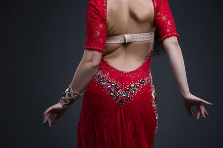 Young beautiful exotic eastern women performs belly dance in ethnic red dress on gray background, studio shot