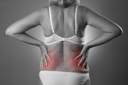 Back pain, kidney inflammation, ache in womans body, black and white photo with red spots