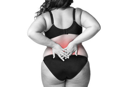 Back pain, fat woman with backache, overweight female body isolated on white background, black and white photo with red spots Reklamní fotografie