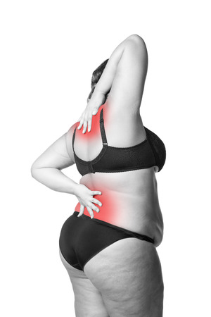 Back and neck pain, fat woman with backache, overweight female body isolated on white background, black and white photo with red spots Stock Photo