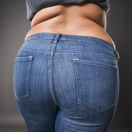 Woman with fat in blue jeans, overweight female body closeup, gray studio background