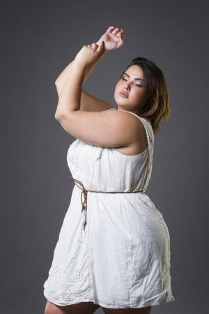 oversized: Plus size fashion model in casual clothes, fat woman on gray studio background, overweight female body