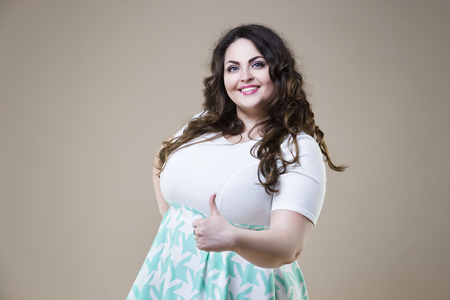 Plus size fashion model in vrijetijdskleding, dikke vrouw op beige studio achtergrond, overgewicht vrouwelijk lichaam