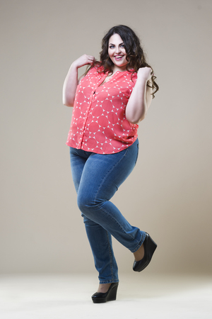 Plus size fashion model in casual clothes, fat woman on beige studio background, overweight female body, full length portrait