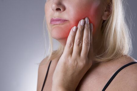 Aged woman with toothache, teeth pain closeup on gray background
