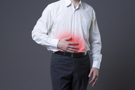 pancreatitis: Man with abdominal pain, stomach ache on gray background, with red dot