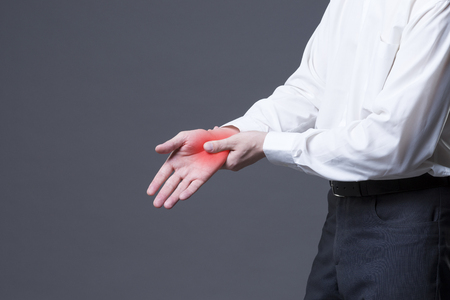 carpal tunnel syndrome: Pain in hand, joint inflammation, carpal tunnel syndrome, studio shot with red dot on gray background Stock Photo