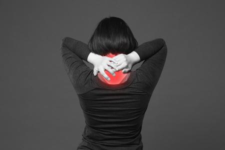 Dolor de cuello, mujer con dolor de espalda sobre fondo gris con puntos rojos