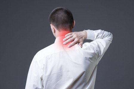 Neck pain, man with backache on gray background with red dots Stock Photo