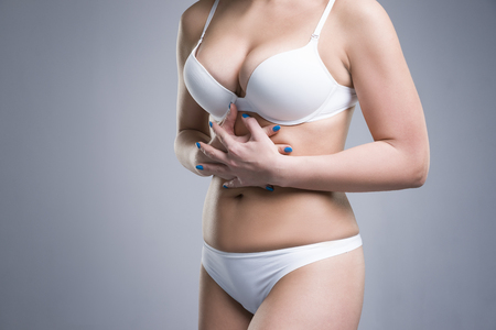 Woman in white underwear with abdominal pain on gray studio background Stock Photo